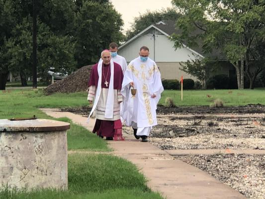 Father Darrell Kostiha of The Church of The Visitation (left) & Bishop Joe sprinkling holy water on the site & foundation area.