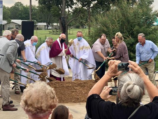 Father Darrell and parishioners participating in the groundbreaking.